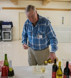 Tom Fischer pouring wine