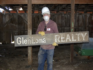 man,hard hat,gloves,sign,glenloma realty,barn,mask